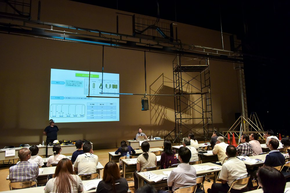 講座内では、照明用のバトンを下ろしてスポットライトの吊り込み作業における落下防止に関する注意事項なども伝えられた。「舞台セットとして、例えば地上に6mの壁があるとき、バトンは下まで下ろすことができません。バトンの下にパイプを吊り下げる(桁吊り)ことで、機材の設置や調整といった精密機器を安全に取り付けることができる」と大石さんはいう。